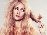: Young woman looking at split ends. Damaged long hair